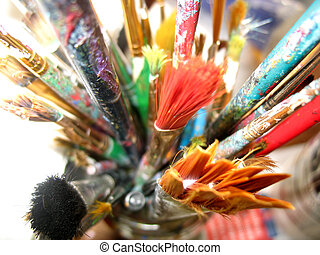 Colourful well used artist brushes in a glass jar.