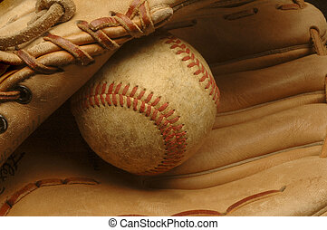A close-up of a well-used baseball nestled in a glove.