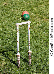 A well used, old croquet Hoop and balls on grass