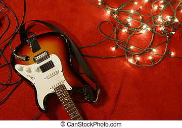 A well used electric guitar laying on a red carpet along with some fairy lights