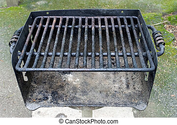 Horizontal close-up shot of a well used public area barbecue grill.
