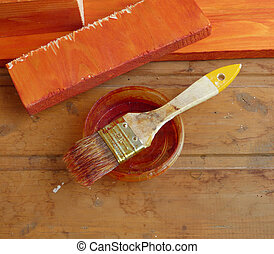 Well-used dirty paintbrush on bank with paint residues. On wooden background with planks behind. Aged home improvement tool.