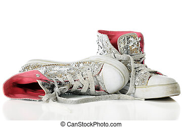 Close-up image of used girls' sparkly sneakers with bright pink linings. On a white background.