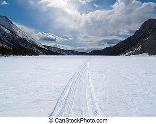 Well used winter trail on frozen mountain lake - Ski-doo ...