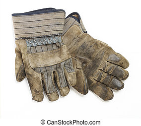 A dirty and well-worn pair of canvas and leather work gloves on white background.