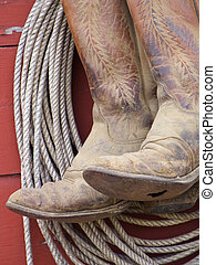 Worn cowboy boots and rope.