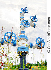 Oil, gas industry. Wellhead with valve armature on a sky background.