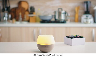 Wellness aromatherapy essential oils diffuser diffusing fragrance into the kitchen. Aroma health essence, welness aromatherapy home spa fragrance tranquil theraphy, therapeutic steam, mental health treatment