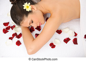 Wellness Massage - Young woman sprinkled with petals on spa...