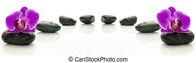 Wellness - Massage stones and purple orchid with water drops...