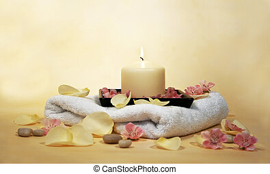 wellness - white towel with yellow candle and rose leaves...