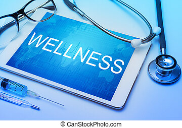 Wellness word on tablet screen with medical equipment on background