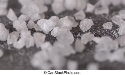 Welsh sea salt flakes on dark background. Close up of minerals droping