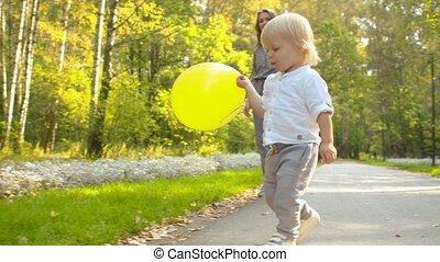wenig, gelber , junge, spielende , baloon