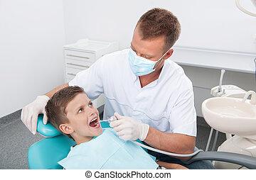 wenig, patient, an, zahnarzt, büro., draufsicht, von, kleiner junge, sitzen, an, der, stuhl, an, der, dentales büro, während, doktor, untersuchen, z�hne