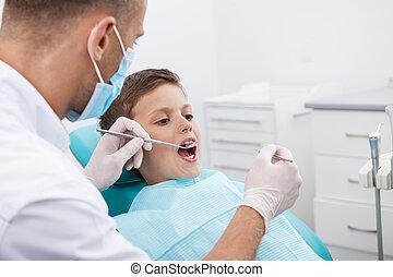 wenig, patient, an, zahnarzt, büro., kleiner junge, sitzen, an, der, stuhl, in, dentales büro, während, doktor, untersuchen, z�hne