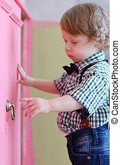 wenig, träumende, junge, öffnet, rosa, tür, von, kabinett, fokus, auf, hand
