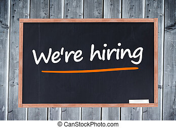 We're hiring written on blackboard against wooden board
