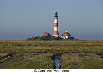 Landscape with salt meadows anad the light house Westerhever located near the coast of the North Sea taken on a sunny morning. This landscape is located near the coast of the North Sea (North Frisia, Germany, Schleswig Holstein):