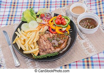 Western Food - Pork steak with brown pepper sauce served...