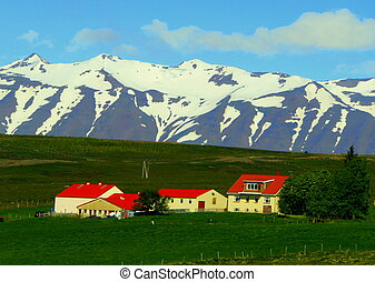 Western Iceland - June 23, 2019 - The view of a farmhouse overlooking snowy mountains along the Ring Road during summer