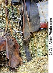 Western saddle. - Western saddle displayed inside a barn.