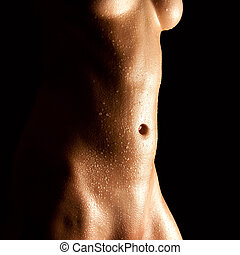 Wet abdomen of a nude young woman in front of black...