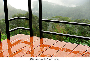 Wet balcony. Behind the valley fog