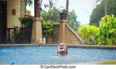 Wet caucasian man gets rained enjoyes while swimming in pool on vacation
