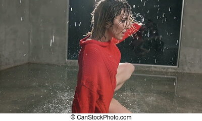 Wet dancer in red sweater is dancing on thew floor with studio light and water rain.