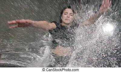 Wet female dancer in black body performs a leap in the rain and splashes of water. The dancer girl who danced under the water during the dance on the stage looks at the camera