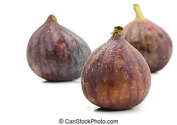 wet fig in front of two figs on white background