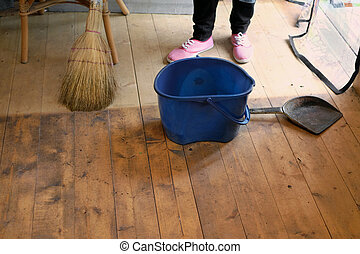Wet floor, broom and dust pan - A housewife cleaning house...