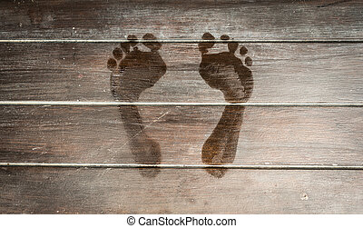 Wet footprints on dark wooden plank floor.