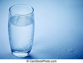 wet glass of water on blue background