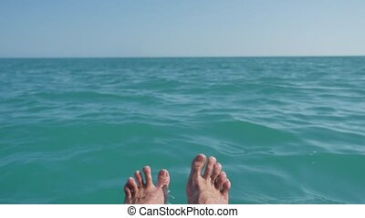 wet man feet on the ocean water. man relaxing his feet over...