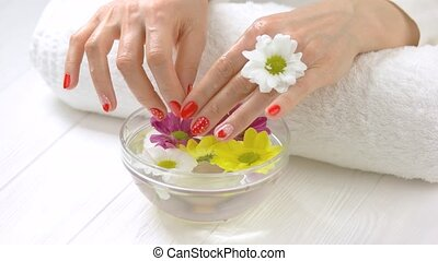 Wet manicured hands in glass bowl. Woman holding hands in...