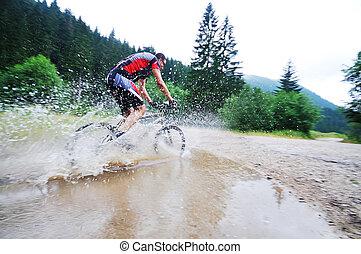 wet mount bike ride - young man drive mountain bike over ...