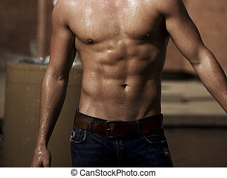 Wet Muscles - A built man\\\'s torso with water streaming...