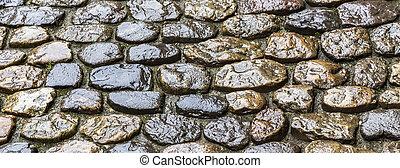 cobble stone road - wet old historic cobble stone road