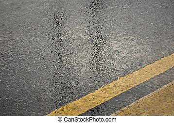 Asphalt road in wet weather with center yellow stripe