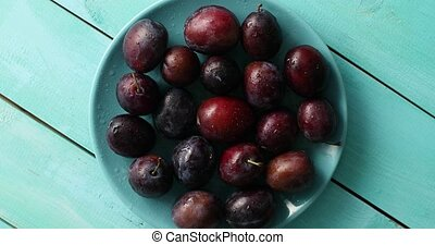 Wet plums on blue plate on table - Top view of pile of fresh...
