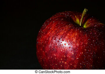 wet red apple in drops of water on a black