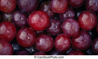 Wet Red Grapes - Closeup of glistening washed grapes turning...