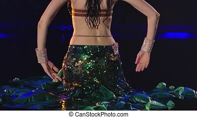 Wet shiny torso of an oriental dancer in raindrops. Woman dancing and shaking her hips in shiny outfit close up. Slow motion
