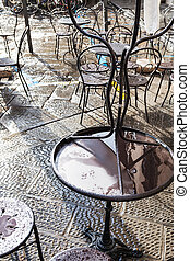 wet tables in street cafe in Florence after rain