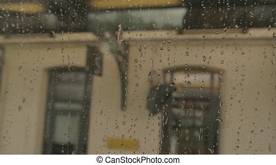 Wet train window. Blurred building and sky. Leave and never...