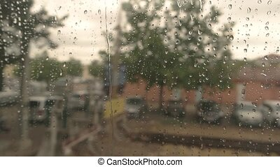 Wet window of train. Blurred town and nature. Leave home...