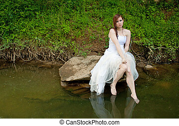 Wet woman sitting on a rock over the water