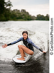 wet woman stands with bent knees on a surfboard and ride down on the splashing wave